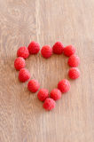 Raspberry in a shape og heart on wooden background. Vertical picture of the raspberries in a shape og heart on wooden background royalty free stock photo