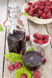 Raspberry Sirup. With fresh fruits on wooden background (detailed close-up shot Royalty Free Stock Image