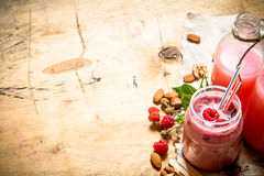 Raspberry smoothie with berries, mint and nuts. On wooden background Royalty Free Stock Photos