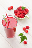 Raspberry smoothie and berries. On white wooden table Royalty Free Stock Photography