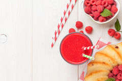 Raspberry smoothie, cake and berries. On wooden table. Top view with copy space Royalty Free Stock Photography