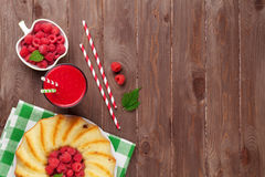 Raspberry smoothie, cake and berries. On wooden table. Top view with copy space Royalty Free Stock Image