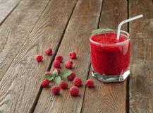 Raspberry smoothie in glass with straw, mint and fresh raspberry. On wood background Royalty Free Stock Photo