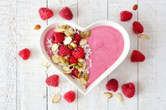 Raspberry smoothie in a heart bowl with superfoods, above on white wood. Healthy raspberry smoothie in a heart shaped bowl with superfoods. Above scene on a Stock Images