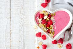 Raspberry smoothie in a heart bowl with superfoods, side border. Healthy raspberry smoothie in a heart shaped bowl with almonds, pumpkin and chia seeds, coconut Stock Photo