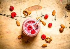 Raspberry smoothie with nuts. On wooden background Royalty Free Stock Photography