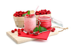Raspberry smoothies, raspberry jam and a basket with ripe raspberries on a white background. Royalty Free Stock Image