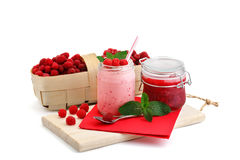 Raspberry smoothies, raspberry jam and a basket with ripe raspberries on a white background. Stock Photos