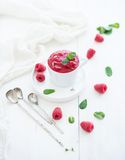 Raspberry sorbet ice-cream with mint leaves  and. Spoons on white background, selective focus Royalty Free Stock Images