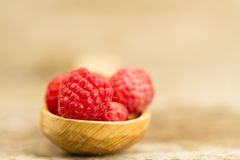 Raspberry in a spoon closeup on wooden background. Ripe raspberry in a spoon closeup on wooden background Stock Photos