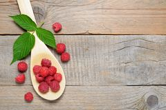 Raspberry in spoon on table. Raspberry in spoon on old wooden table Royalty Free Stock Image