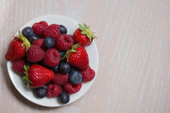 Raspberry, strawberry, bilberry on the white plate Stock Image
