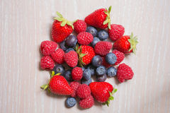 Raspberry, strawberry and bilberry on the wooden background. Group of fruit:raspberry, strawberry and bilberry Royalty Free Stock Image