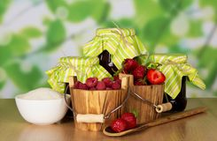 Raspberry and strawberry jam. Jam, buckets with raspberry and strawberry a cup with sugar and a spoon with berries on a table Royalty Free Stock Photos