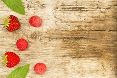 Raspberry and strawberry with mint leaves on wooden background Stock Image