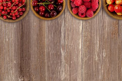 Raspberry, strawberry, pomegranate, currant in a wooden bowls. Stock Photos