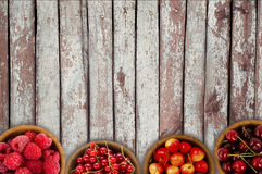 Raspberry, strawberry, pomegranate, currant in a wooden bowls. Top view. Royalty Free Stock Image