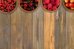 Raspberry, strawberry, pomegranate, currant in a wooden bowls. Top view. Royalty Free Stock Photography