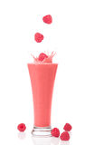 Raspberry and Strawberry Smoothie. A glass of raspberry and strawberry smoothie with raspberries splashing into the glass Royalty Free Stock Images