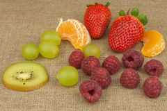Raspberry, strawberry, tangerine, grapes and kiwi on a canvas background. Healthy food on the kitchen table Royalty Free Stock Photo