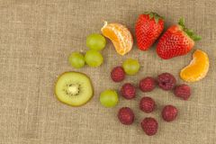 Raspberry, strawberry, tangerine, grapes and kiwi on a canvas background. Healthy food on the kitchen table Stock Photos
