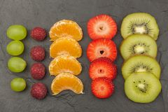 Raspberry, strawberry, tangerine, grapes and kiwi on a slate background. Healthy food on the kitchen table. Royalty Free Stock Images