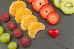 Raspberry, strawberry, tangerine, grapes and kiwi on a slate background. Healthy food on the kitchen table. Royalty Free Stock Photo