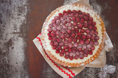 Raspberry tart with fresh raspberries on top. A whole raspberry tart with powdered sugar and fresh raspberries. Top view, vintage toned image, blank space Royalty Free Stock Images
