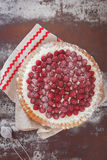 Raspberry tart with fresh raspberries. A whole raspberry tart with powdered sugar and fresh raspberries. Top view, vintage toned image, blank space Stock Photo