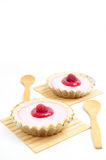 Raspberry tarts. Two raspberry tarts with wooden coasters and spoons Royalty Free Stock Image