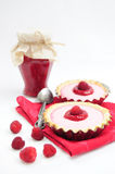 Raspberry tarts and jar of raspberry jam. Two tarts with raspberry cream, jar of jam and raspberry fruits Stock Photos