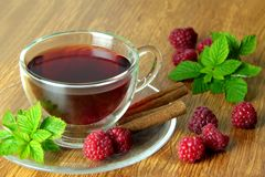 Raspberry tea with cinnamon spices. Fresh raspberries on background. Hot raspberry tea flavoured by cinnamon spice Royalty Free Stock Images