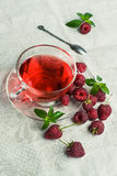 Raspberry tea in a glass cup stock image