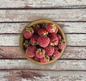 Raspberry top view. Sweet raspberries on a wooden background. Raspberry in a wooden bowl with copy space for text Royalty Free Stock Photo