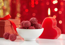 Raspberry truffles and burning candle Royalty Free Stock Photo