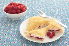 Raspberry turnovers. On a plate, with a bowl of fresh raspberries in the background Stock Photos