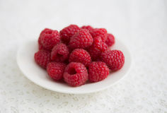 Raspberry on the white plate. On the lace background Royalty Free Stock Image