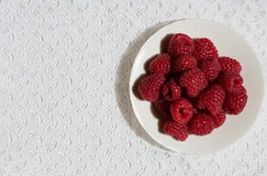 Raspberry on the white plate. On the lace background Stock Images