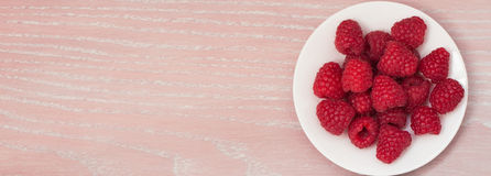 Raspberry on the white plate. On the wooden background Stock Images