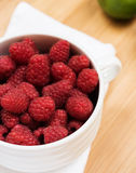 Raspberry in white plate. On wooden table, closeup Royalty Free Stock Photos