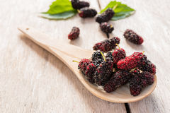 Raspberry  on wood spoon on wood floor. Red and black raspberry  on wood spoon on wood floor Stock Images