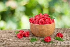 Raspberry in a wooden bowl on table with a blurry garden background.  Royalty Free Stock Photography