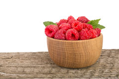 Raspberry in a wooden bowl on table with white background.  Stock Photos