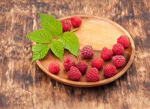 Raspberry on a wooden plate. Raspberry on a wooden background in a plate Royalty Free Stock Image