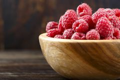Raspberry in a wooden plate. Ripe raspberries on a wooden background in a wooden plate. delicious berry for making jam Stock Images