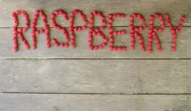 Raspberry word of fresh berries on wooden background with copy space.  Stock Image