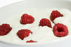 Raspberry in yogurt. Several crimson berries in a bowl with vanilla yogurt royalty free stock photography