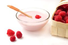 Raspberry yogurt in a glass cup with raspberry basket on a white background.  Stock Photo