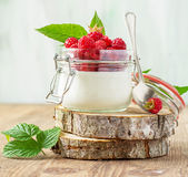 Raspberry and yogurt. Jar of fresh homemade yogurt with fresh raspberries ripe for breakfast on a wooden background. The concept of healthy natural foods Stock Photos