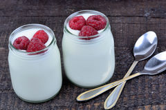 Raspberry with yogurt in a jars on table. Raspberry with yogurt in a jars on wooden table Royalty Free Stock Photos